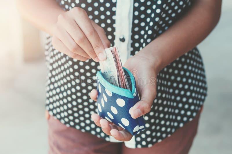 Χέρια που κρατούν τη μικρή σακούλα χρημάτων λογαριασμών τραπεζών στοκ φωτογραφία