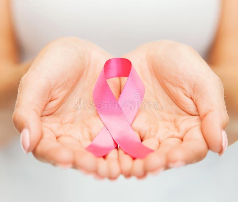 Χέρια που κρατούν τη ρόδινη κορδέλλα συνειδητοποίησης καρκίνου του μαστού στοκ εικόνα με δικαίωμα ελεύθερης χρήσης