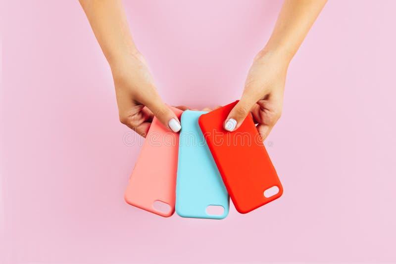 Χέρια που κρατούν τις ζωηρόχρωμες περιπτώσεις smartphone στοκ εικόνα