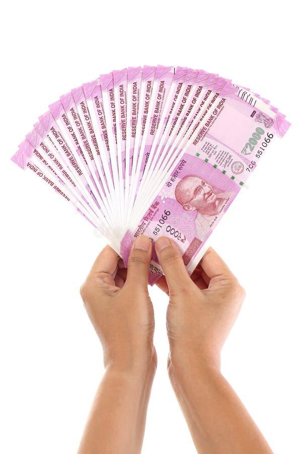 Χέρια που κρατούν τις ινδικές σημειώσεις ρουπίων του 2000 ενάντια στο λευκό στοκ εικόνες