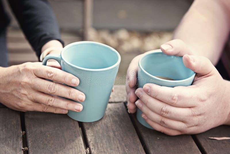 Χέρια που κρατούν τις φλυτζάνες τσαγιού στοκ φωτογραφία