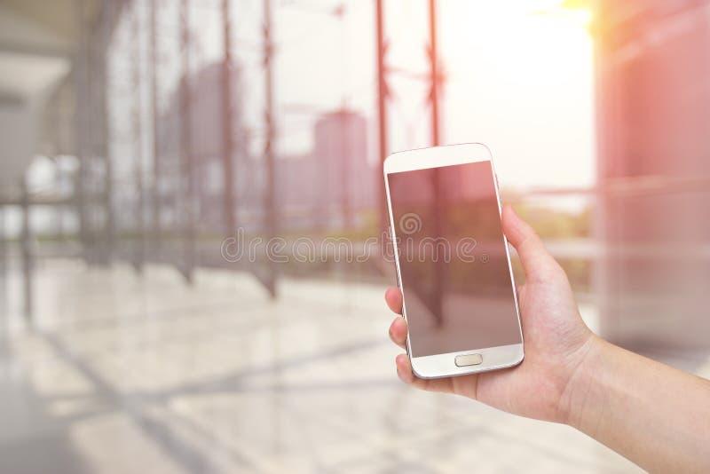 Χέρια που κρατούν το έξυπνο τηλέφωνο με το θολωμένο έννοια υπόβαθρο κατασκευής εφαρμοσμένης μηχανικής στοκ φωτογραφία με δικαίωμα ελεύθερης χρήσης