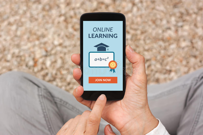 Χέρια που κρατούν το έξυπνο τηλέφωνο με τη σε απευθείας σύνδεση έννοια εκμάθησης στην οθόνη στοκ εικόνα