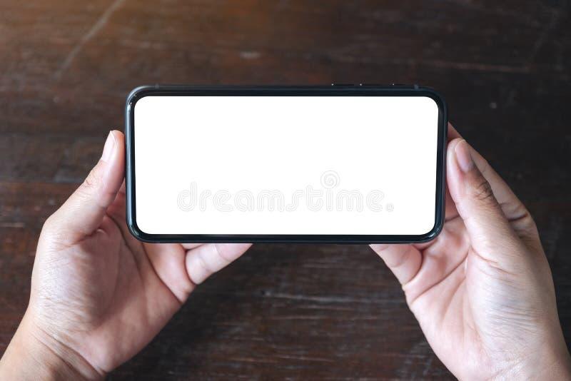 Χέρια που κρατούν το μαύρο κινητό τηλέφωνο με την κενή οθόνη υπολογιστών γραφείου οριζόντια στο ξύλινο επιτραπέζιο υπόβαθρο στοκ φωτογραφίες