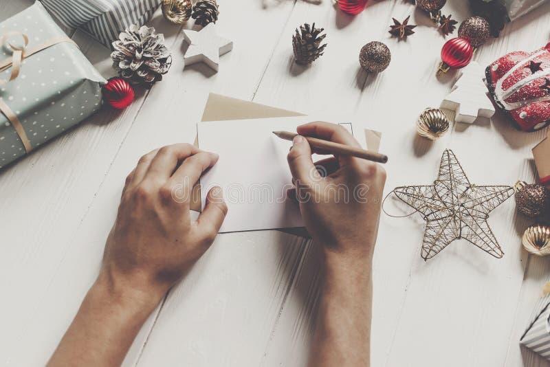Χέρια που κρατούν το μολύβι και που γράφουν μια λίστα επιθυμητών στόχων επιστολών στο cla santa στοκ φωτογραφία με δικαίωμα ελεύθερης χρήσης