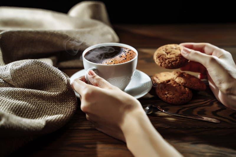 Χέρια που κρατούν το μπισκότο και τον καφέ στον ξύλινο πίνακα στοκ εικόνα με δικαίωμα ελεύθερης χρήσης