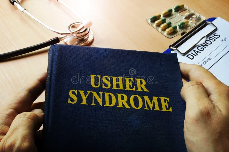 Χέρια που κρατούν το σύνδρομο του Usher βιβλίων στοκ φωτογραφία με δικαίωμα ελεύθερης χρήσης