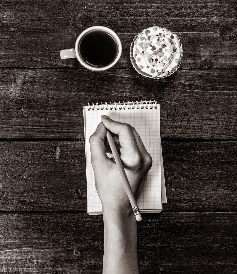 Χέρια που κρατούν το φλυτζάνι σημειωματάριων στοκ φωτογραφία με δικαίωμα ελεύθερης χρήσης