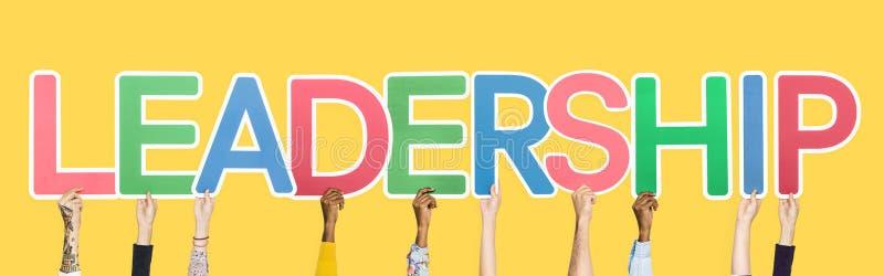 Χέρια που κρατούν ψηλά τις ζωηρόχρωμες επιστολές που διαμορφώνουν την ηγεσία λέξης στοκ εικόνες