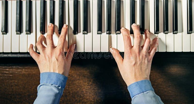 Χέρια που παίζουν το πιάνο στοκ εικόνες