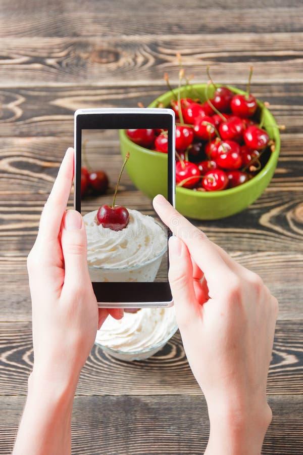 Χέρια που παίρνουν τη μαρμελάδα κερασιών φωτογραφιών με το smartphone στοκ εικόνες