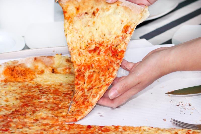 Χέρια που παίρνουν τις φέτες της πίτσας Μαργαρίτα Το χέρι που επισύρεται την προσοχή στα κομμάτια της εύγευστης πίτσας, κλείνει ε στοκ εικόνες