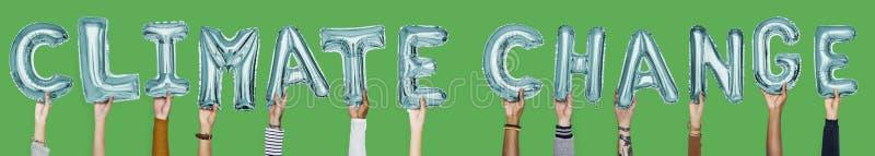 Χέρια που παρουσιάζουν λέξη μπαλονιών κλιματικής αλλαγής στοκ εικόνα με δικαίωμα ελεύθερης χρήσης