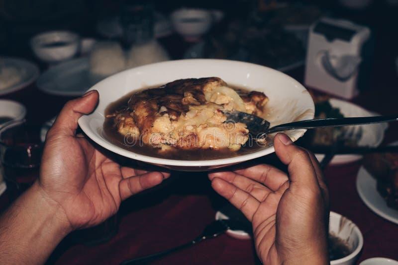 Χέρια που περνούν ή που μοιράζονται το πιάτο της κινεζικής κουζίνας αυγών γύρω από τον πίνακα κατά τη διάρκεια του γεύματος στοκ φωτογραφία με δικαίωμα ελεύθερης χρήσης