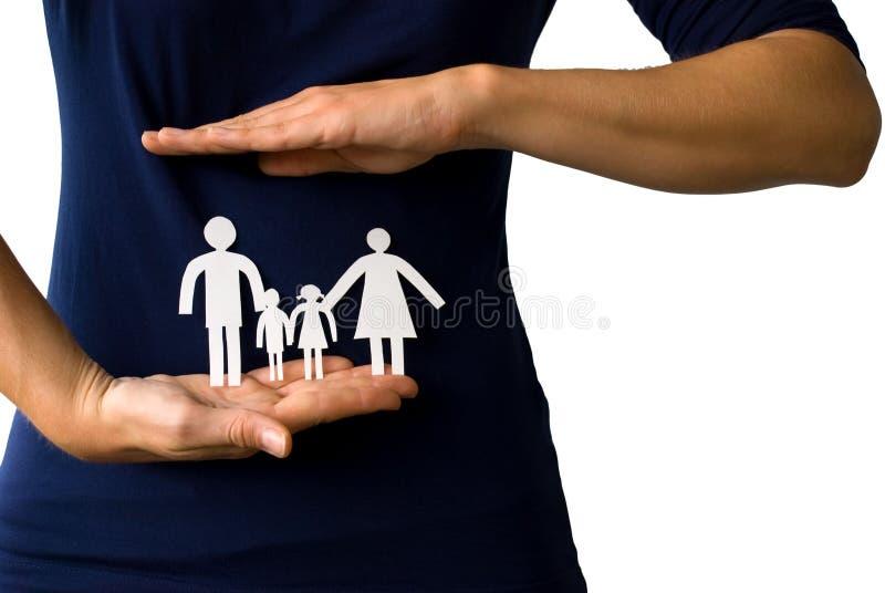 Χέρια που προστατεύουν μια οικογένεια αλυσίδων εγγράφου στοκ φωτογραφία με δικαίωμα ελεύθερης χρήσης