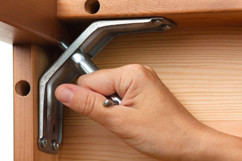 Χέρια που συγκεντρώνουν τα ξύλινα έπιπλα με το γαλλικό κλειδί στοκ εικόνα