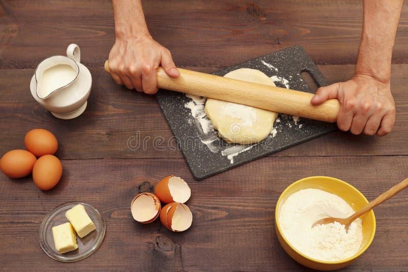 Χέρια σεφ που κυλούν ζύμη με κυλινδρικό πείρο πάνω στο ξύλινο τραπέζι στοκ φωτογραφία
