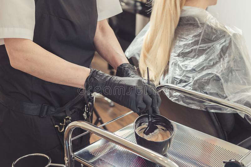 Χέρια στιλίστων τρίχας που προετοιμάζουν μια χρωστική ουσία σε ένα εμπορευματοκιβώτιο στοκ φωτογραφία με δικαίωμα ελεύθερης χρήσης