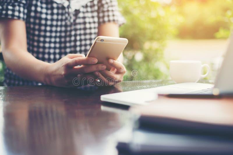 Χέρια της γυναίκας hipster που χρησιμοποιεί το smartphone στη καφετερία με μαλακό στοκ φωτογραφίες