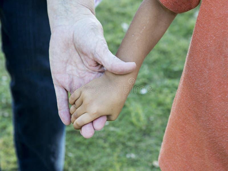 Χέρια της ηλικιωμένης κυρίας και του μικρού παιδιού στοκ εικόνες
