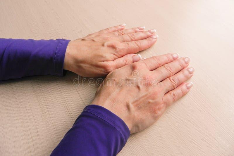 Χέρια της μέσης ηλικίας γυναίκας με τις παλάμες κάτω Πρότυπο στο υπόβαθρο γραφείων Κινηματογράφηση σε πρώτο πλάνο προτύπων με το  στοκ φωτογραφία με δικαίωμα ελεύθερης χρήσης