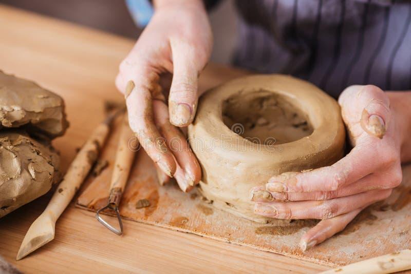 Χέρια της νέας γυναίκας που κάνει το χωμάτινο δοχείο στον ξύλινο πίνακα στοκ φωτογραφίες με δικαίωμα ελεύθερης χρήσης
