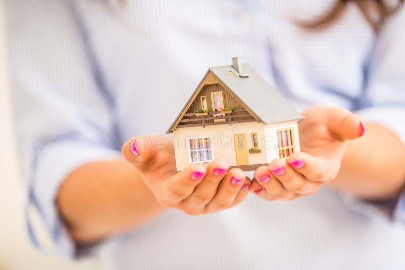Χέρια της νέας γυναίκας που κρατά το πρότυπο σπίτι στοκ εικόνες