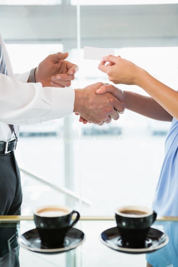 Χέρια τινάγματος επιχειρηματιών και δόσιμο της επαγγελματικής κάρτας στο συνάδελφο στοκ εικόνες