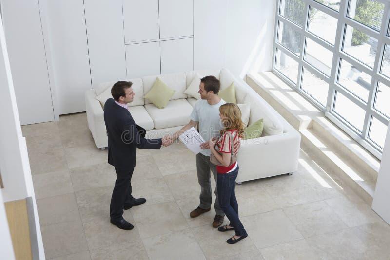 Χέρια τινάγματος κτηματομεσιτών με τον άνδρα από τη γυναίκα στο νέο σπίτι στοκ φωτογραφία
