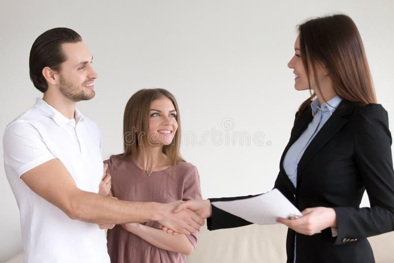 Χέρια τινάγματος παντρεμένου ζευγαριού με το κτηματομεσίτη στο νέο σπίτι στοκ εικόνες με δικαίωμα ελεύθερης χρήσης