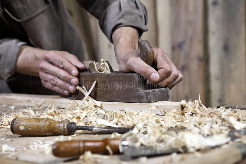 Χέρια του αεροπλάνου ξυλουργών στον πάγκο εργασίας στην ξυλουργική στοκ φωτογραφίες
