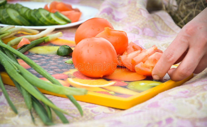 Χέρια του αρχιμάγειρα που κόβει μια ντομάτα στοκ φωτογραφίες με δικαίωμα ελεύθερης χρήσης