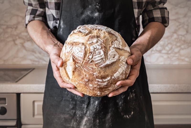 Χέρια του ατόμου που κρατά τη μεγάλη φραντζόλα του άσπρου ψωμιού Αρσενικό στο μαύρο apro στοκ φωτογραφία με δικαίωμα ελεύθερης χρήσης