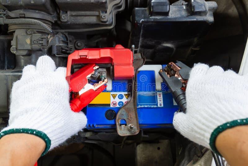 Χέρια του αυτοκίνητου τεχνικού που χρησιμοποιεί τα καλώδια αλτών στη φόρτιση της μπαταρίας οχημάτων στοκ εικόνα