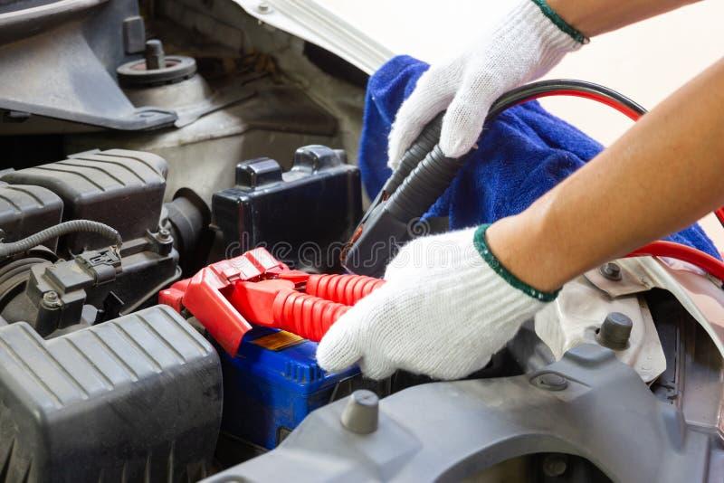 Χέρια του αυτοκίνητου τεχνικού που χρησιμοποιεί τα καλώδια αλτών στη φόρτιση της μπαταρίας οχημάτων στοκ φωτογραφία με δικαίωμα ελεύθερης χρήσης