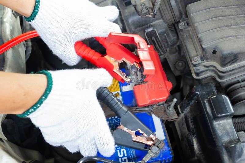 Χέρια του αυτοκίνητου τεχνικού που χρησιμοποιεί τα καλώδια αλτών στη χρέωση στοκ εικόνα
