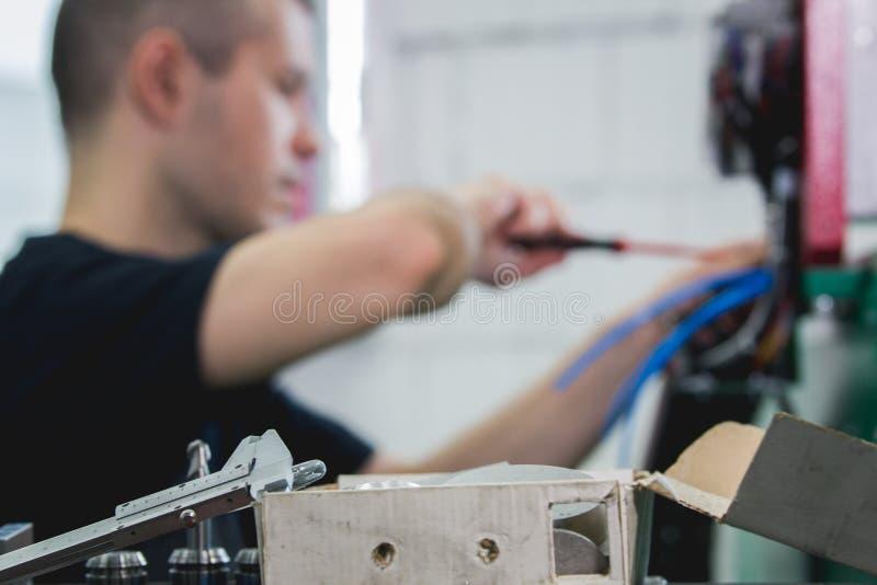Χέρια του βιδώματος μηχανικών ηλεκτρολόγων και του εξοπλισμού δοκιμής στο κιβώτιο θρυαλλίδων, de-στραμμένα στοκ φωτογραφία με δικαίωμα ελεύθερης χρήσης