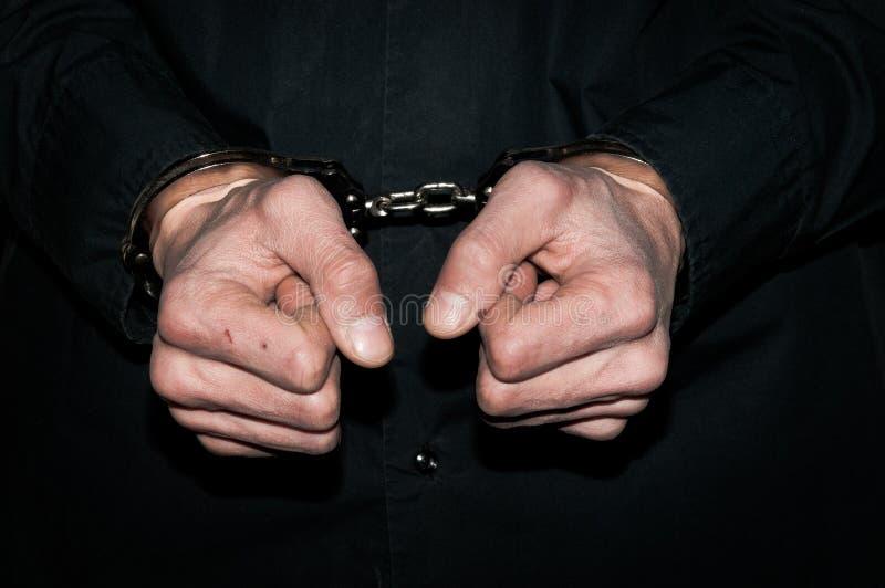 Χέρια του δεμένου με χειροπέδες εγκληματικού ατόμου στο μαύρο πουκάμισο στοκ εικόνα με δικαίωμα ελεύθερης χρήσης