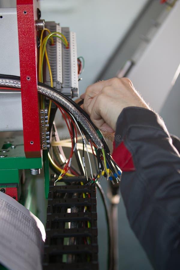 Χέρια του εξοπλισμού μετατροπής και δοκιμής μηχανικών ηλεκτρολόγων στοκ φωτογραφία
