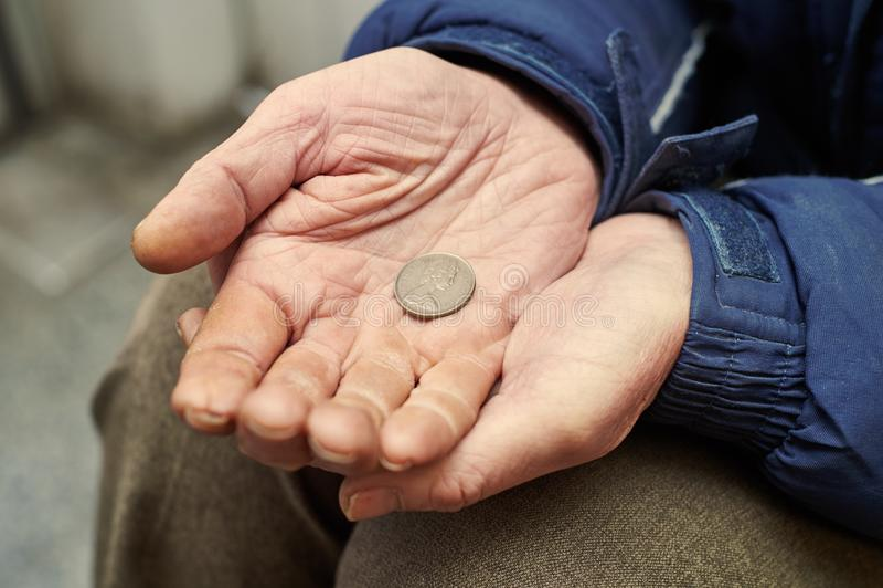 Χέρια του επαίτη με το νόμισμα πενών που ικετεύει για τα χρήματα στοκ εικόνα