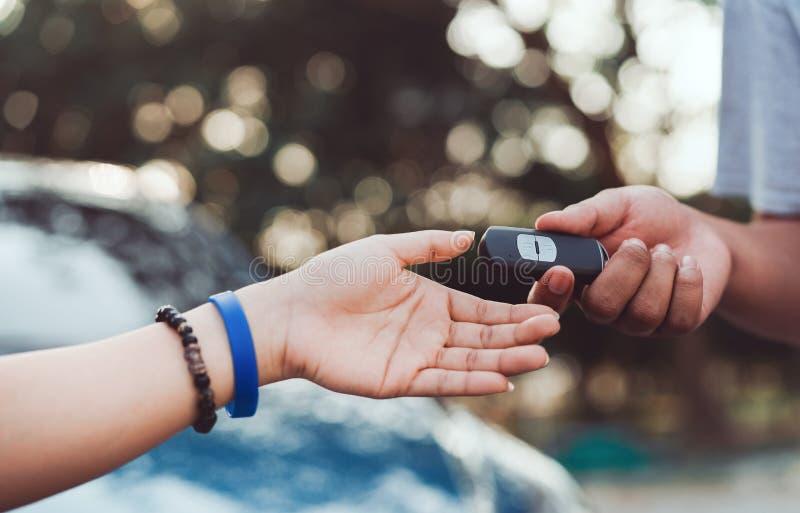 Χέρια του επαγγελματικού εμπόρου που δίνουν το κλειδί συστημάτων αυτοκινήτων στοκ φωτογραφία