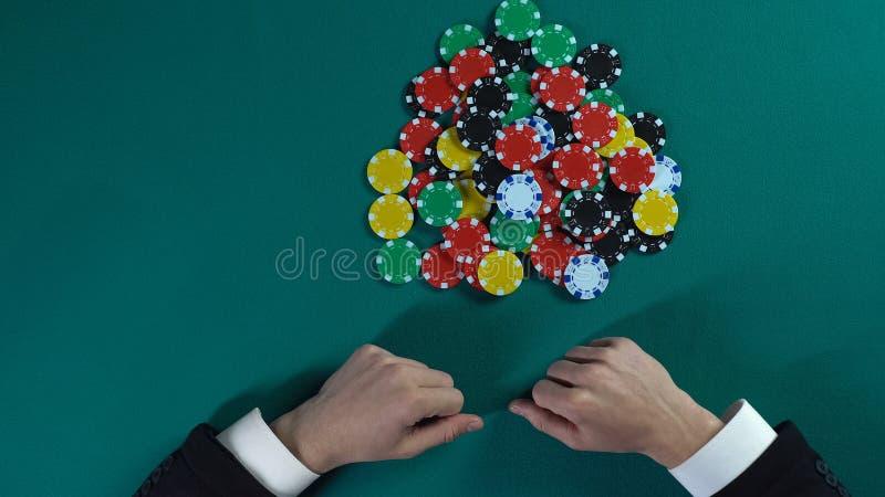 Χέρια του επιχειρηματία που παίρνουν όλα τα τσιπ στη χαρτοπαικτική λέσχη, μονοπώλιο στην αγορά, τοπ άποψη στοκ φωτογραφίες με δικαίωμα ελεύθερης χρήσης