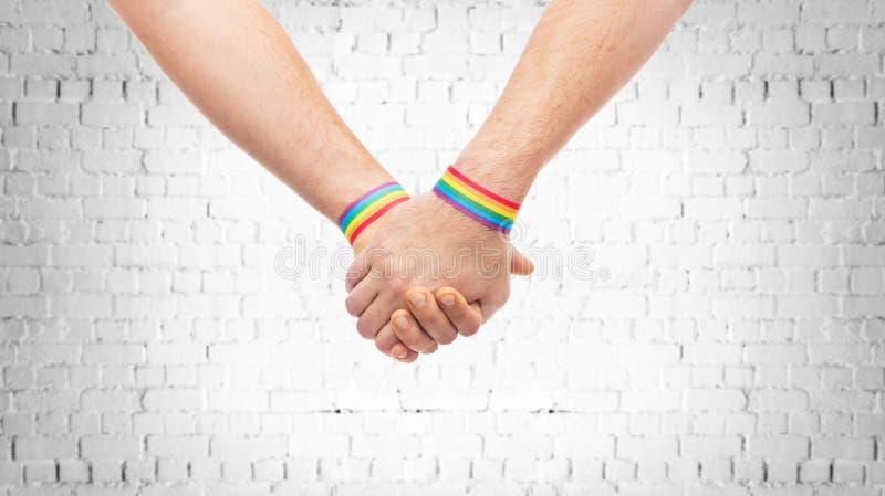 Χέρια του ζεύγους με το ομοφυλοφιλικό ουράνιο τόξο υπερηφάνειας wristbands στοκ εικόνες