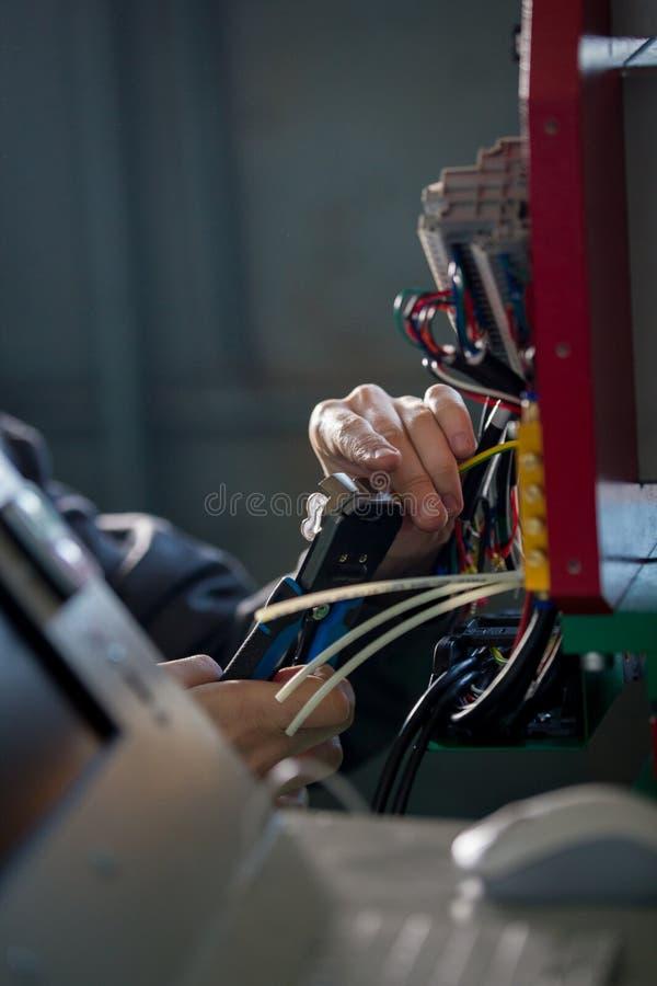 Χέρια του ηλεκτρολόγου με stripper που εγκαθιστά το ενεργειακό σύστημα στη βιομηχανία μηχανημάτων στοκ φωτογραφία