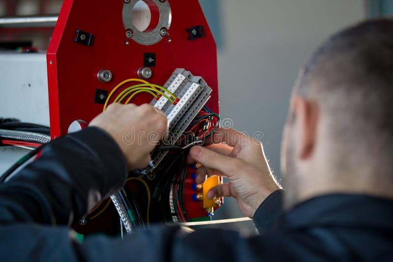 Χέρια του ηλεκτρολόγου με stripper που εγκαθιστά το ενεργειακό σύστημα στη βιομηχανία μηχανημάτων στοκ φωτογραφίες
