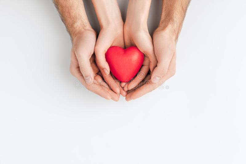 Χέρια του ηλικιωμένου ατόμου και μικρότερου που κρατά την κόκκινη καρδιά απομονωμένη στο άσπρο υπόβαθρο στοκ φωτογραφία με δικαίωμα ελεύθερης χρήσης