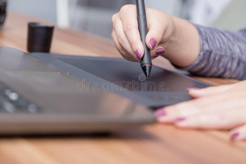 Χέρια του θηλυκού σχεδιαστή στο γραφείο που λειτουργεί με την ψηφιακή γραφική ταμπλέτα Δημιουργικοί άνθρωποι ή επιχειρησιακή έννο στοκ φωτογραφία με δικαίωμα ελεύθερης χρήσης
