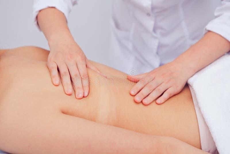 Χέρια του μασέρ που τρίβει τη θηλυκή πλάτη στοκ φωτογραφία με δικαίωμα ελεύθερης χρήσης