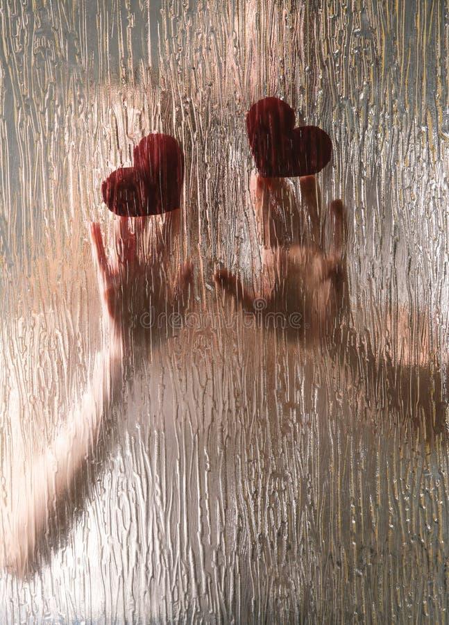 Χέρια του νέου ζεύγους με τις καρδιές στοκ φωτογραφία με δικαίωμα ελεύθερης χρήσης