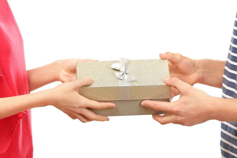 Χέρια του νέου κιβωτίου δώρων εκμετάλλευσης ζευγών αγάπης στο άσπρο υπόβαθρο στοκ φωτογραφία με δικαίωμα ελεύθερης χρήσης